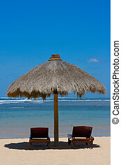 Two lounge chairs under tent on beach