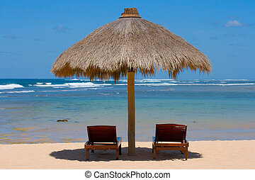 Two lounge chairs under tent on beach - Two wooden lounge...