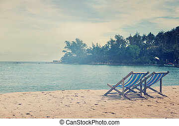 two loungers on the beach, with a retro image toning