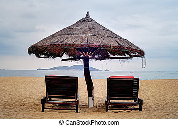 Two loungers under straw parasol at the beach