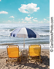 Two loungers under sun umbrella at the beach