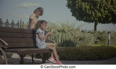Two lovely little girls networking with cellphone