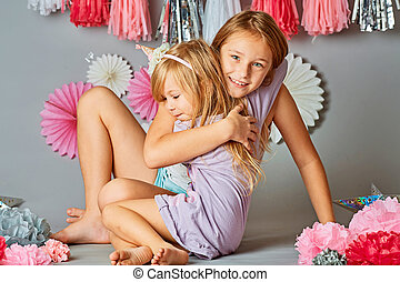 Two lovely little girls playing on the floor