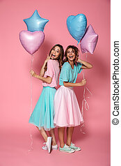 Two lovely young girls dressed in bright colorful clothes