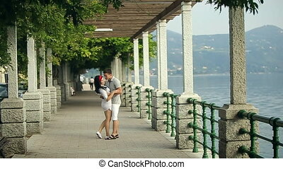 Two Lovers Embrace and Kiss in the Park