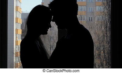 Two lovers embracing and kissing. Silhouette.