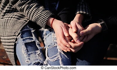 Two lovers holding hands sitting on a bench at the street.
