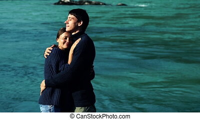 Two lovers hugging on the background of blue water