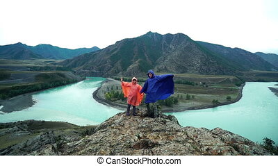 Two lovers in raincoats are standing on the edge of the mountain and waving their arms. Back view