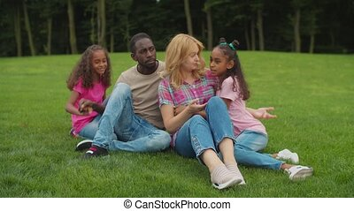 Two loving daughters embracing parents in nature - Two cute ...