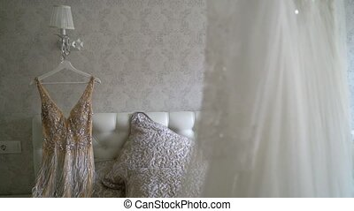 Two luxury wedding dress hanging in bedroom - white and...