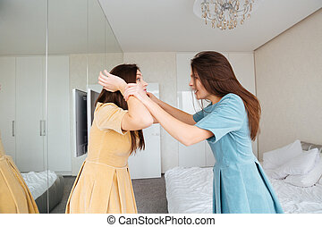 Two mad irritated young sisters twins arguing in bedroom -...
