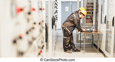 Two maintenance engineers inspect relay protection system with laptop comp
