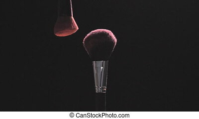 Two Make-up brushes with pink powder on a black background -...