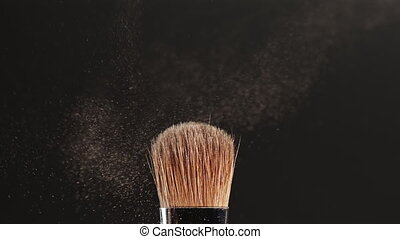 Two makeup brushes touch each other on black background and small particles of cosmetics - shadows fly apart, effect of explosion. Beauty industry, instruments, slow motion