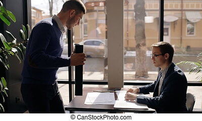 Two male business partners is meeting at cafe, greeting,...