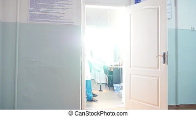 Two male caucasian doctors come out cabinet and view mri picture, showing something on x-ray to each other, later move farther. Colleagues walking at hospital. Light on background. Low angle of view