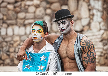 Pair of handsome male cirque performers outside
