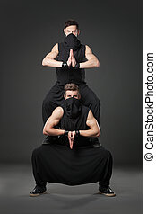 Two male dancers posing in ninja costumes on dark gray background.