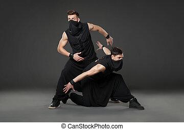 Two male dancers posing in ninja costumes on dark gray...