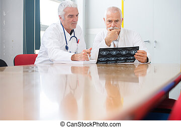 two male doctors discussing x-rays at the table