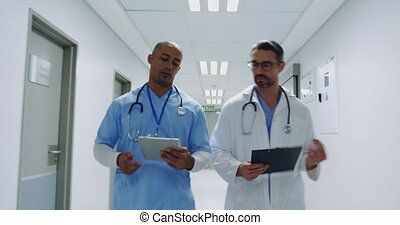Two male doctors talking as they walk in hospital corridor 4k
