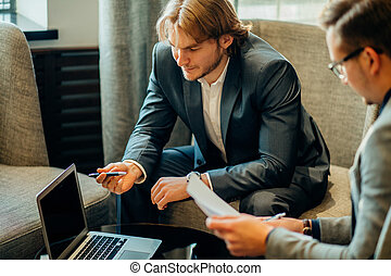 Two male employees consulting with laptop in cafe