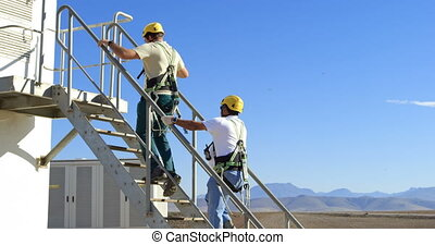 Two male engineer walking upstairs on wind mill 4k - Two...