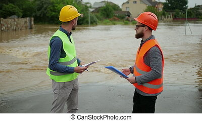 Two male engineers solve the flood problem. Natural disaster major flooding underwater entire community and neighborhood flooded. Homes, houses overflowing with water, home insurance needed.