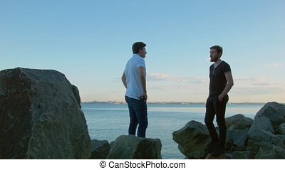 Two male friends communicate standing on stones against the background of the sea.