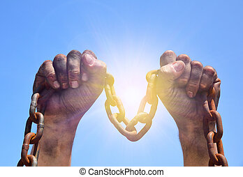 Two male hands are raised upwards with an iron rusty chain...