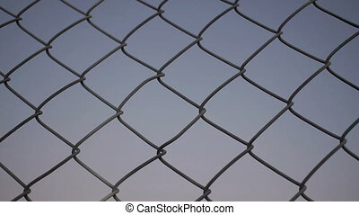Two Male Hands Grabbing Wire Fence - Closeup evening or dusk...