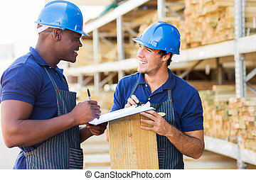 hardware store workers working in timber yard - two male ...