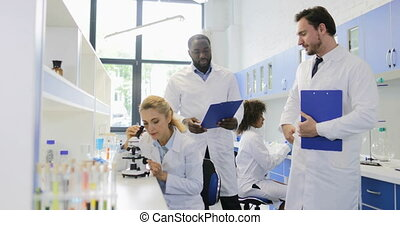 Two Male Scientists Discussing Results Of Study With Woman Working With Microscope In Modern Laboratory, Team Od Researchers Talking Slow Motion 60