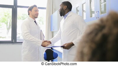 Two Male Scientists Handshake In Laboratory Congradulating With Successful Experiment Results Over Busy Team Of Scientific Workers