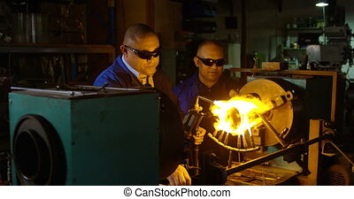 Two male workers creating glass in glass factory. Workers heating glass 4k
