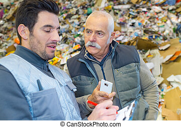 two male workers in recycling center