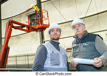 two male workers with cherry picker in background