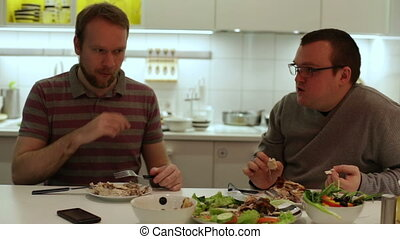 Two man eating chicken and vegetables