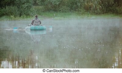 Two man fishing on the rubber boat in the forest lake....