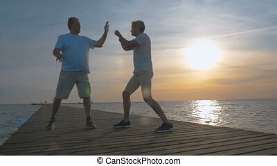 Two man having boxing training on the pier