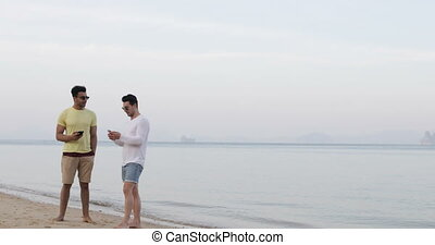 Two Man On Beach Talking, Using Cell Smart Phones Gay Couple...