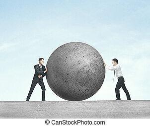 two man pushing ball - two businessman pushing concrete ball