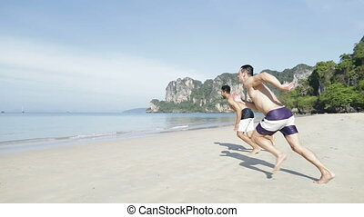 Two Man Running In Water On Beach, Young Male Couple On Sea...