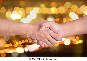 two man shaking hands on city bokeh background