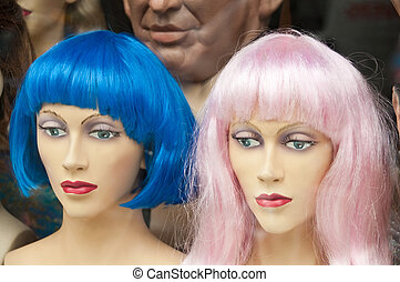 Two Mannikin heads with colorful wigs in a wig store - Two...