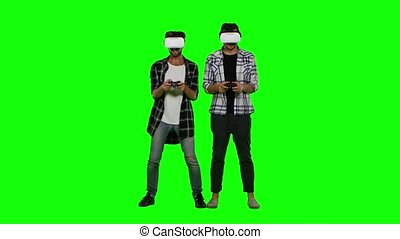 Two mans playing game using VR-helmet. Green screen - Two...