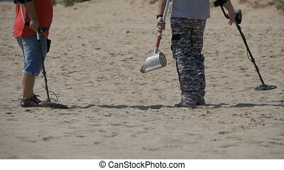 Two Mans with a Metal Detector Walks along a Sandy Beach on...