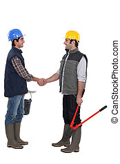Two manual workers greeting each other
