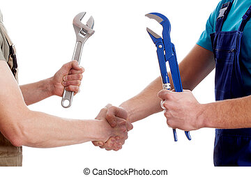Two manual workers shaking their hands